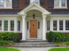 Elegant Wooden Front Door Of Large Suburban House With Gabled Portico