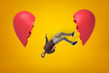 Young Man In Casual Clothes Falling Between Two Broken Heart Pieces On Yellow Background