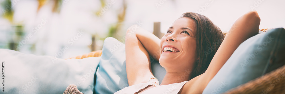 Fototapeta Relaxing home lifestyle happy woman in relax luxury hotel room sofa lying back with arms behind head smiling. Asian girl in comfortable lounging chair travel living.