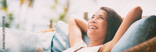 Poster Relaxation Relaxing home lifestyle happy woman in relax luxury hotel room sofa lying back with arms behind head smiling. Asian girl in comfortable lounging chair travel living.