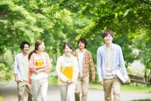 新緑の中を歩く大学生