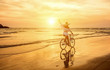 Leinwandbild Motiv Happiness woman traveler with her bicycle rides on sea coastline