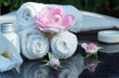 Set for outdoor spa treatments, folded white towels, soap, lotion and fragrant flowers