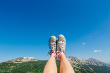 Feet In Silver Sneakers Up Infront Of The Blue Sky And Mountains