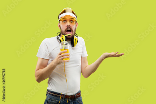 Half-length close up portrait of young man in shirt on yellow background. Male model with headphones and drink. The human emotions, facial expression, summer, weekend concept. Astonished and surprised - 267910785