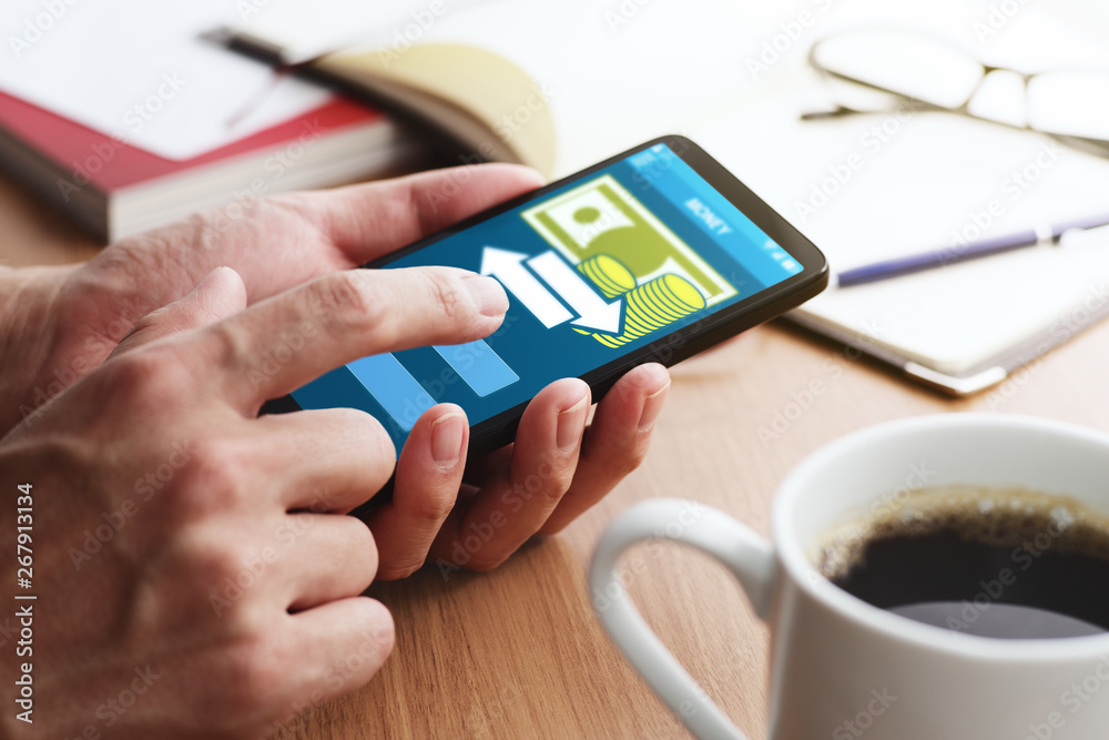 Fototapeta Using smartphone for money transfer and banking.Closeup of male hands touching smartphone screen for using app at table.