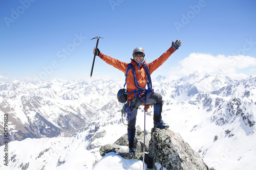 Obraz na płótnie mountaineer with ice ax stands on the top of a mountain in the background of the