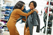 Two models african american woman in brown tunic dress posed at boutique clothes store. It's time for shopping.