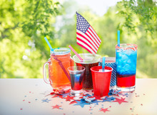 Independence Day, Celebration And Holidays Concept - Close Up Of Drinks In Cups And Glasses With American Flag At 4th July Party Over Green Natural Background