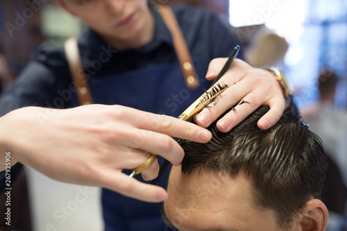 grooming, hairdressing and people concept - close up of male client and hairdresser with comb and scissors cutting hair at barbershop