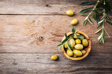 Fresh Green Olives In A Bowl And Olive Branch On Rustic Wooden Background, Top View