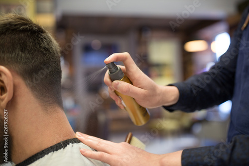grooming, hairdressing and people concept - hairstylist applying styling spray to male client's hair at barbershop