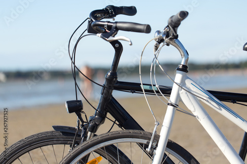 leisure, transport and sport concept - close up of two bicycles on beach