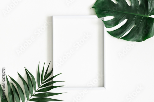 Obraz Summer composition. Tropical palm leaves, white photo frame on white background. Summer, nature concept. Flat lay, top view, copy space - fototapety do salonu