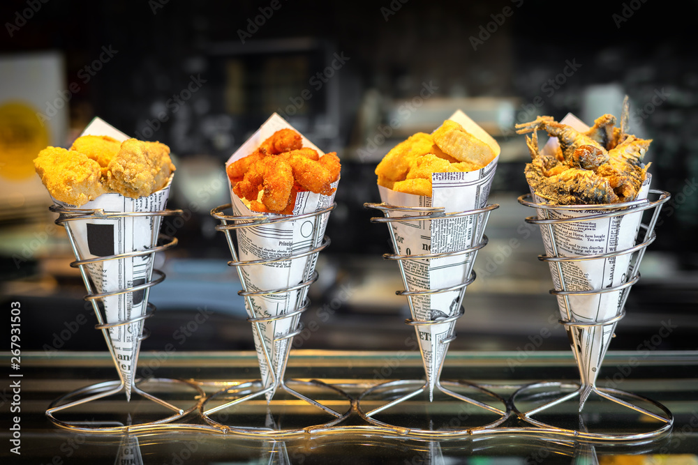 Fototapety, obrazy: Sea food in cones at counter in small street shop in Spain – snack with mixed takeaway grilled fish and fried seafood – to go delicious roasted octopus, anchovies and calamari ready to eat by tourists