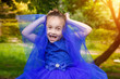 Leinwandbild Motiv Young girl in birthday blue dress in park. Smile child outdoor