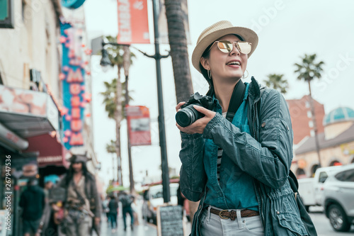 Fotografia young asian female photographer holding slr camera smiling taking picture on street outdoor sunny day