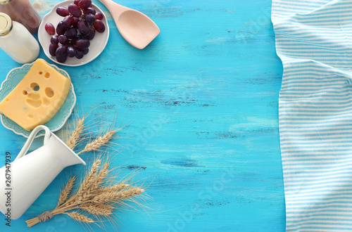 Tuinposter Londen Top view photo of dairy products over blue wooden background. Symbols of jewish holiday - Shavuot