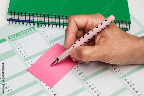 Obraz na plátne  Mano de mujer escribiendo sobre post it y calendario vista desde arriba