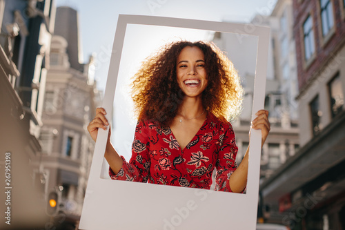 Excited girl with empty photo frame