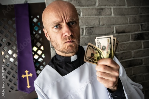 Catholic priest with money in his hand Canvas Print
