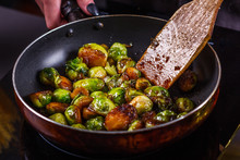 Young Woman Fries Brussels Sprouts On A Frying Pan