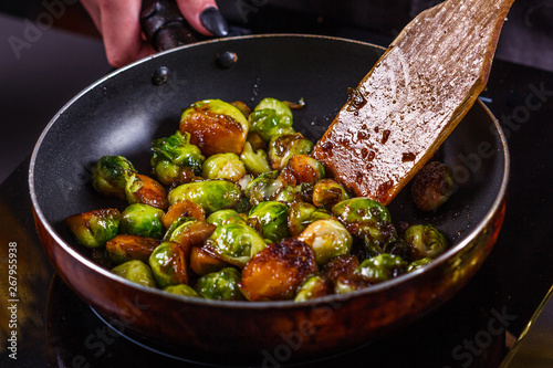 Fotografie, Obraz young woman fries Brussels sprouts on a frying pan
