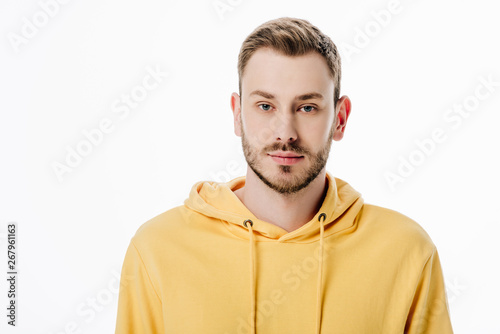 handsome thoughtful man in yellow hoodie looking at camera isolated on white