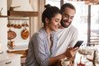 Photo of smiling brunette couple drinking coffee and using cell phone during breakfast at home
