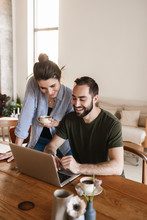 Image Of Candid Brunette Couple Working On Laptop Together While Sitting At Table At Home