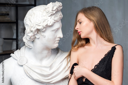 Young woman embracing God Apollo bust sculpture  Ancient