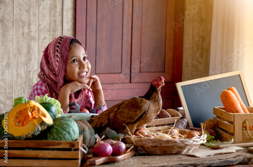 Fotografía  Asian little young girl look forward and smile among various types of vegetable