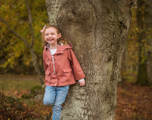 Little Girl Leans On A Tree In...