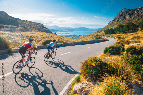 Road cycling photo. Two triathlete train in beautiful nature. Sea and mountains in background. Alcudia, Mallorca, Spain