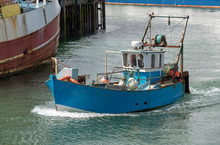 Portsmouth, England, UK, May 2019. A Small Blue And White Painted Fishing Boat Enters The Fishing Port.