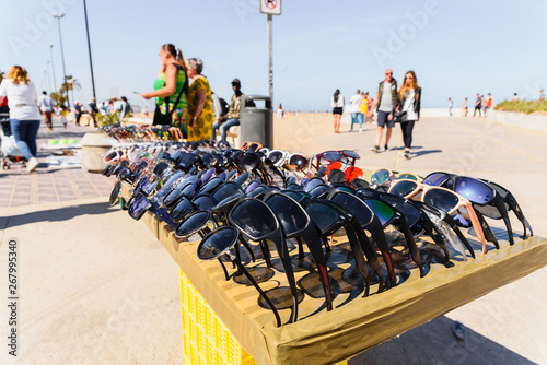 Valencia, Spain - May 12, 2019: Illegal immigrants selling false glasses and souvenirs to tourists on the beach of Valencia Billede på lærred