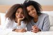 Leinwandbild Motiv Head shot portrait of African American mother and daughter on bed