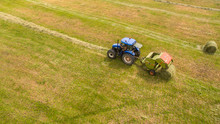 Bird Eye Of Man At Work On The Tractor With Hay Baler