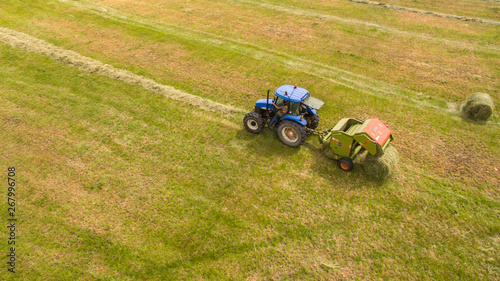 bird eye of Man at work on the tractor with hay baler Wallpaper Mural