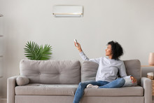 Smiling African American Woman Using Air Conditioner Remote Controller