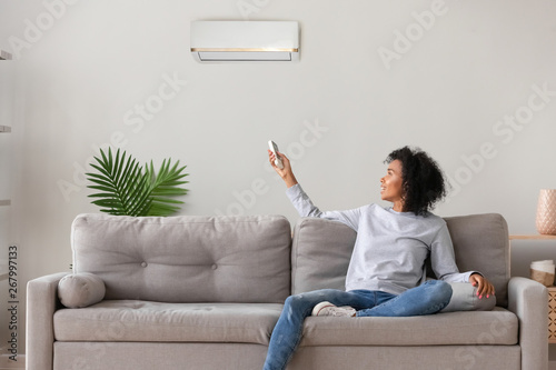 Photo Smiling African American woman using air conditioner remote controller