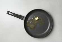 Frying Pan With Melting Butter On Grey Table, Top View