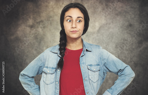 Portrait of an annoyed female teenager on a grungy background Canvas Print