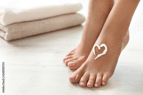 Closeup view of woman with cream on her foot indoors, space for text. Spa treatment