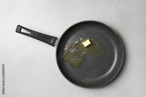 Valokuvatapetti Frying pan with melting butter on grey table, top view