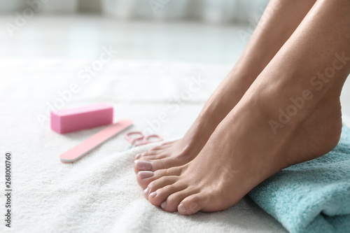 Woman with beautiful feet and pedicure accessories on white towel, closeup. Spa treatment