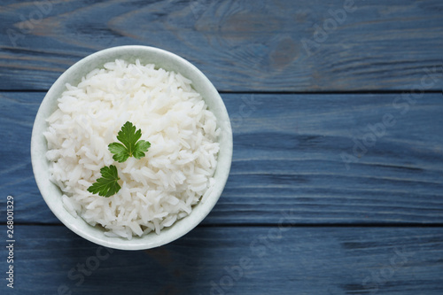 Fotografie, Obraz  Bowl of cooked rice with parsley on wooden background, top view