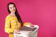 Leinwandbild Motiv Happy young woman holding basket with laundry on color background, space for text