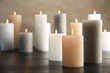 Leinwanddruck Bild - Burning candles on table against color background. Space for text