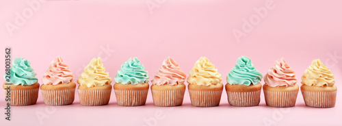Row of delicious cupcakes on color background, space for text Canvas Print